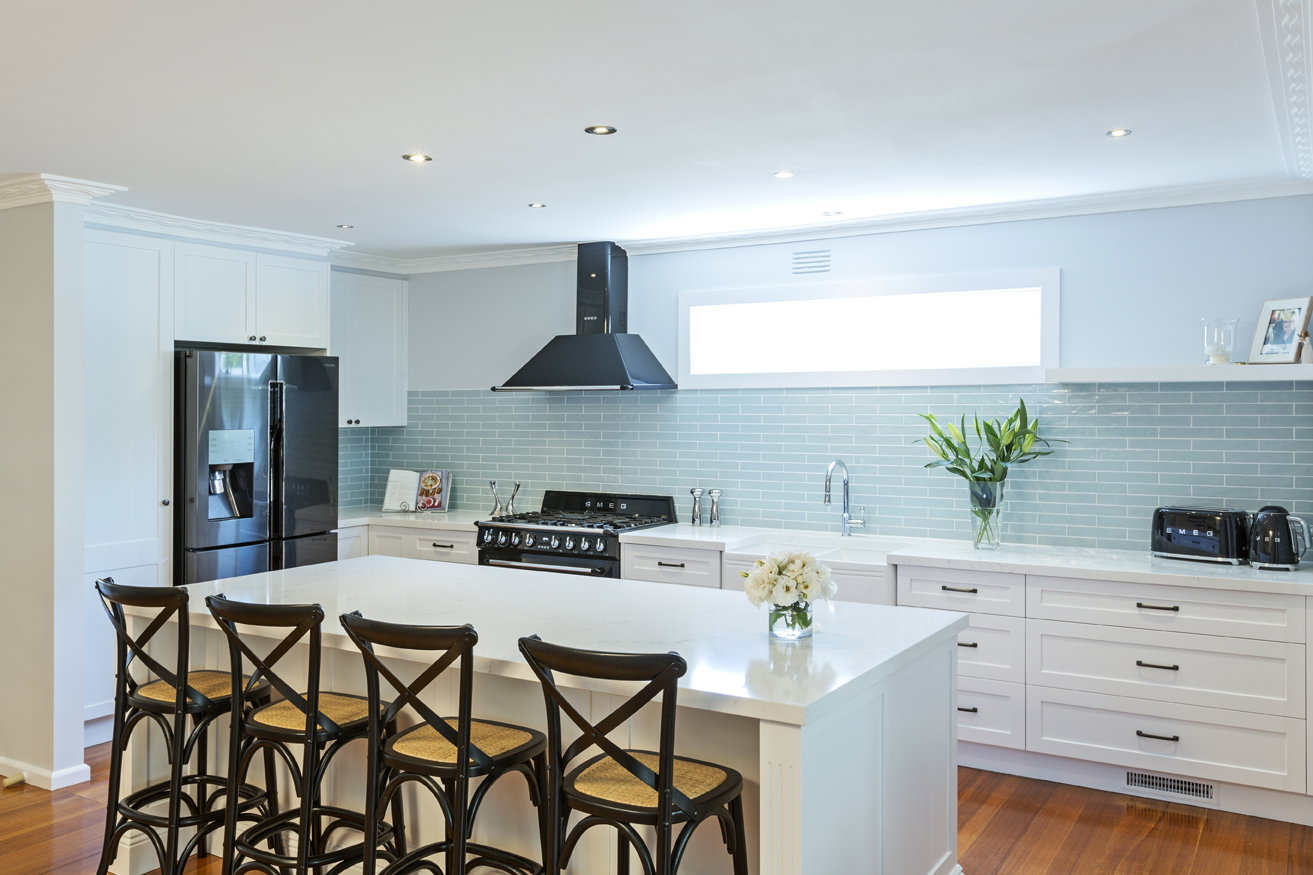 white kitchen with island and stools at a breakfast bar