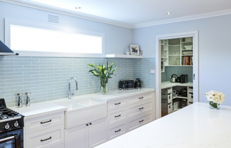 white kitchen with light blue tiles and wallpaper, door leading to extra storage