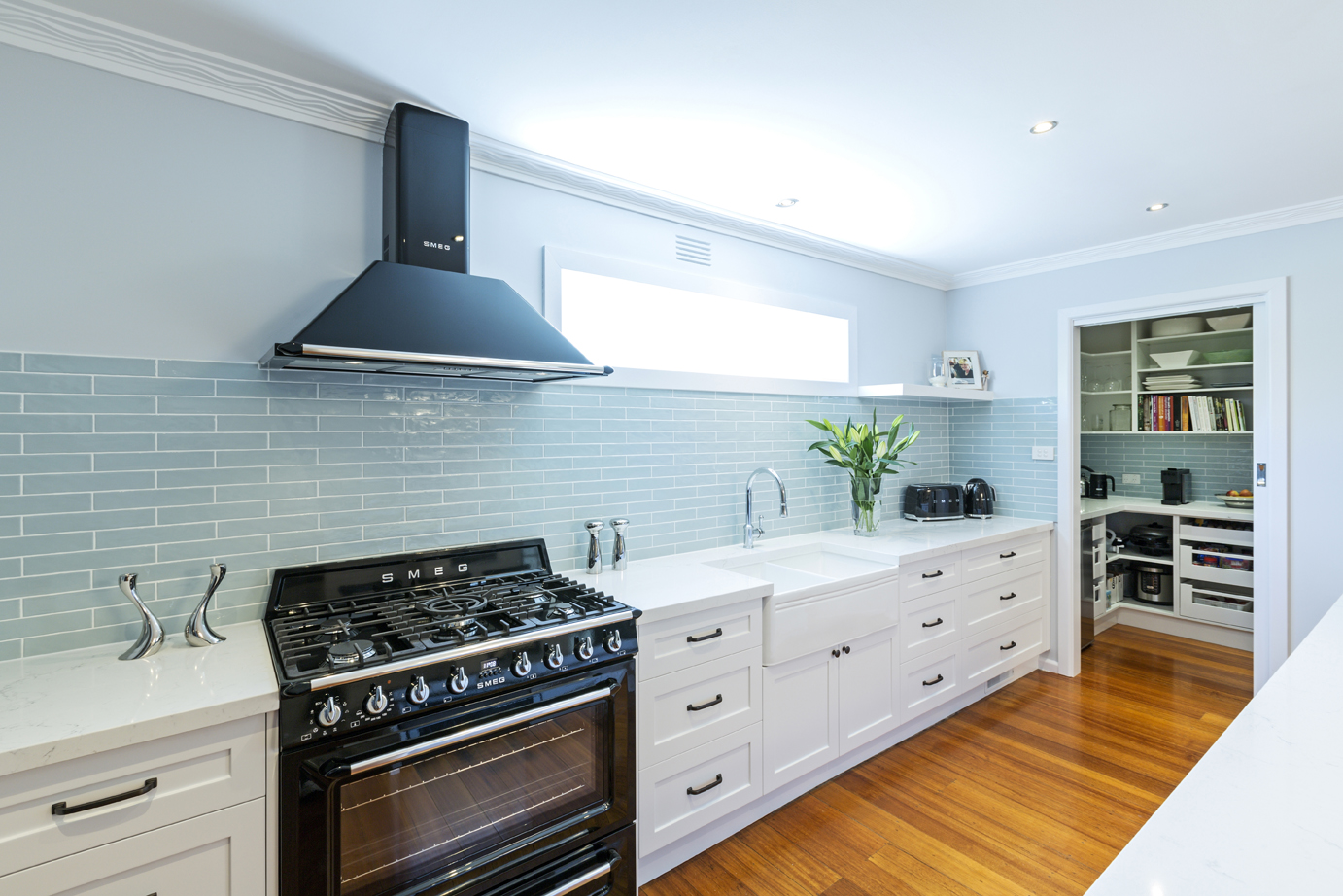 white kitchen with hardwood floors, SMEG oven and extra storage room