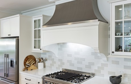 white kitchen with stovetop and large exhaust hood