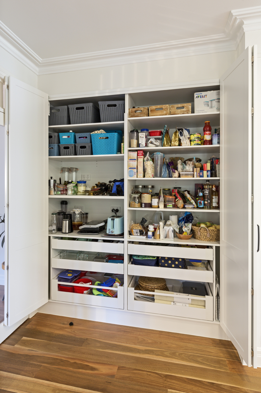 long open cupboard with food and kitchen goods inside
